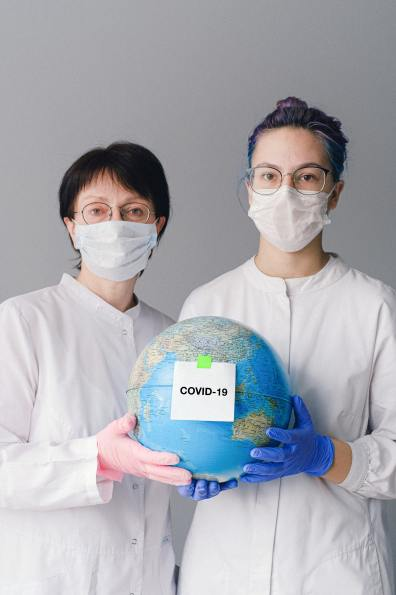 people-with-face-masks-and-latex-gloves-holding-a-globe-4167562